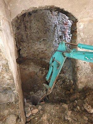Un escavatore in azione in un edificio storico